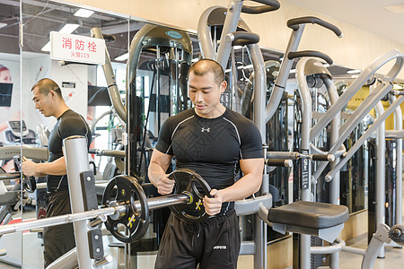 健身房男人组装举重杠铃片图片