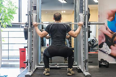 健身房强壮男人挺举训练图片