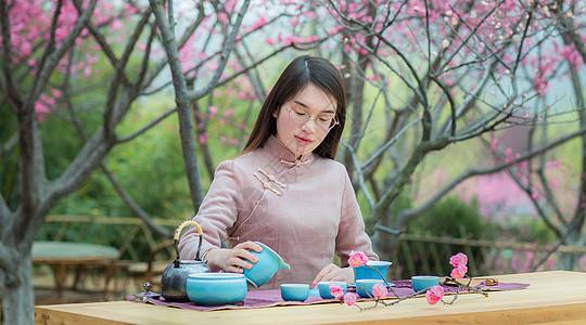 女子在梅花树下泡茶图片