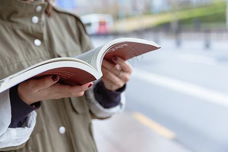 公交亭边等车边看书的女生图片