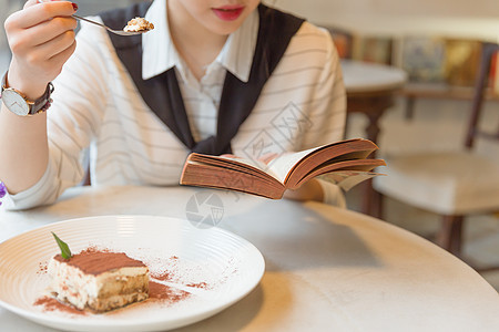 咖啡馆内女孩边吃甜品边看书图片