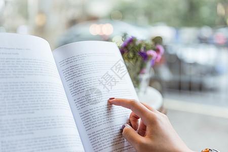 咖啡馆美女手点书本看书特写图片