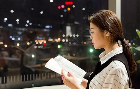 落地窗前夜晚女孩看书图片