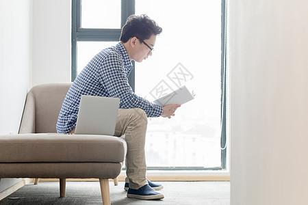 坐在沙发上看书的年轻人图片