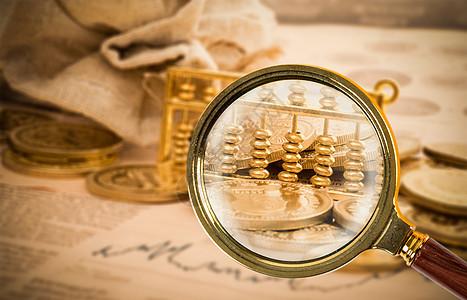 放大镜照亮金币算盘图片