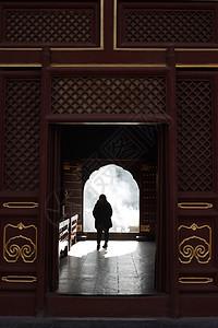 一个信佛的老人独自穿过北京雍和宫的宫殿图片