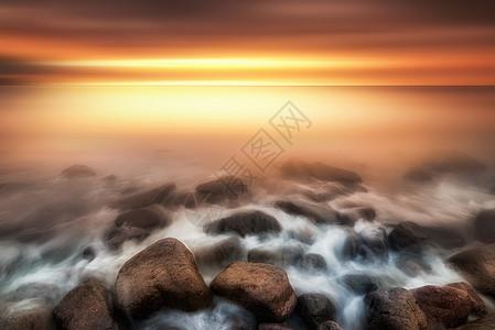 阳光下海边岩石上的拉丝海浪图片