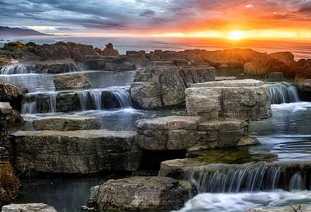 阳光下的海边的石头和瀑布图片