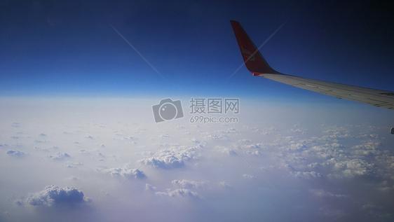 蓝天下云层上的飞行图片