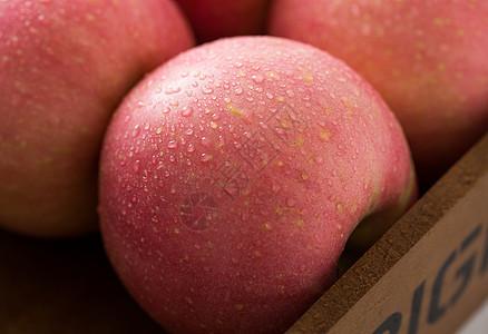 带着露水的红苹果放在木盘子里图片