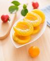 一盘黄桃罐头放在实木桌子上的特写图片