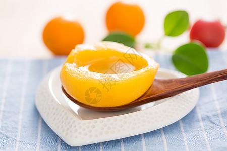 一片蜜桃罐头放在小盘子里图片