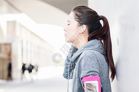 年轻女子健身后听音乐放松图片