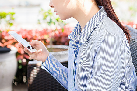年轻女性户外使用手机休闲放松图片