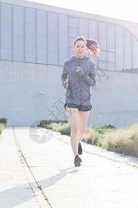 夕阳下跑步运动的年轻女性图片