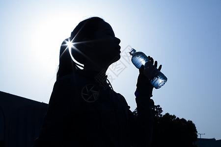 年轻女性健身运动喝水剪影图片