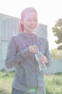 年轻女性户外运动休息喝水图片