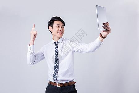 商务男士拿着电脑庆祝成功图片