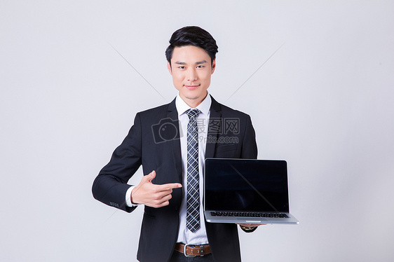商务男士手拿电脑展示介绍图片