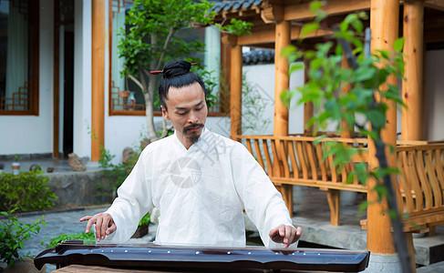 一位白衣道士在古老的院子里弹古琴图片
