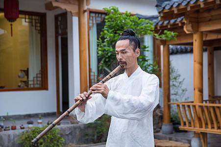 一位白衣道士在庭院内吹奏长笛图片