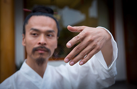 一位白衣道士在院子里练习武术的手部面部特写图片