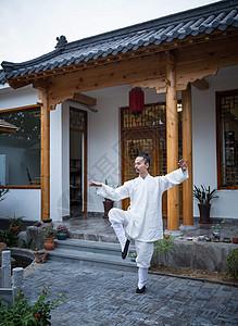 一位道士在古老的房屋前练习武术图片