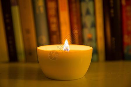 一杯燃烧的蜡烛放在书桌旁图片