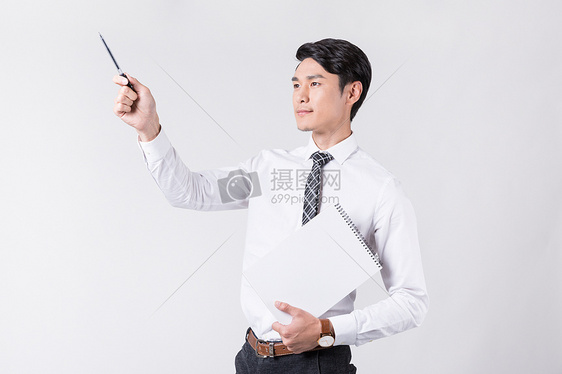 商务男士拿着笔和纸看向远方图片
