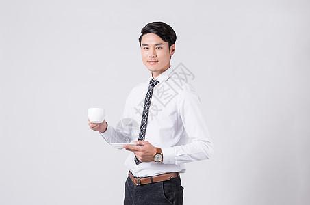 时尚商务男士端着咖啡喝咖啡图片