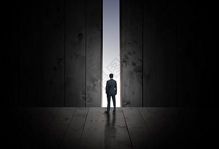 商务人士面向木墙的背影图片