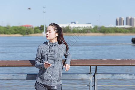 运动女孩靠栏杆休息听音乐图片