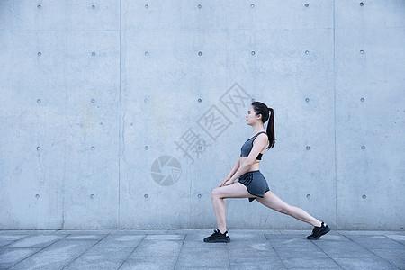 户外运动女孩热身压腿图片
