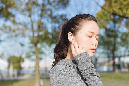 公园运动女孩阳光下休息听音乐图片