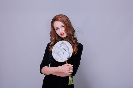 中国旗袍卷发美女手持团扇图片