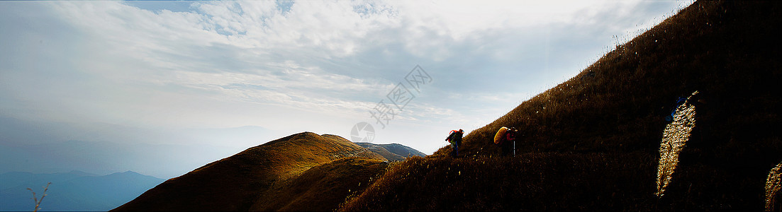 高山上背着东西行走的人图片
