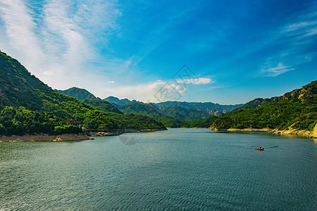 蓝天白云下的山谷间的湖面和小船图片