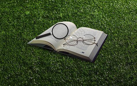 草地风格放大镜和书图片