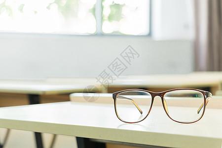 教室里书桌上的眼镜特写图片