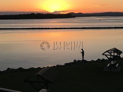 夕阳海滩垂钓图片
