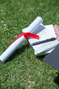 大学草地上的书本证书学士帽图片