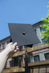 大学教室前手拿学士帽的人图片