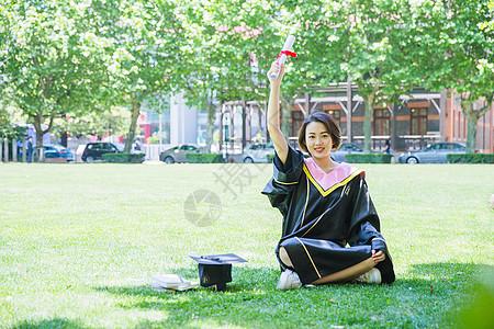 坐在草地上清新学士服女学生图片