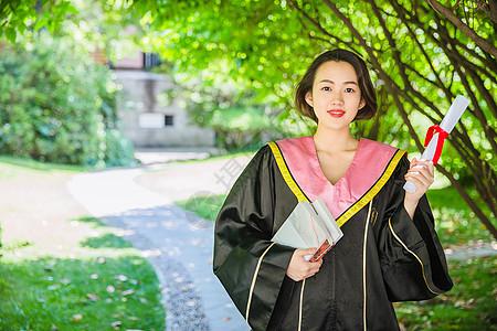 毕业季穿学士服抱书的学生图片