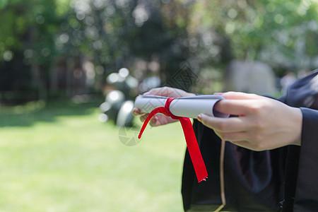 草地上手递毕业证的学生图片