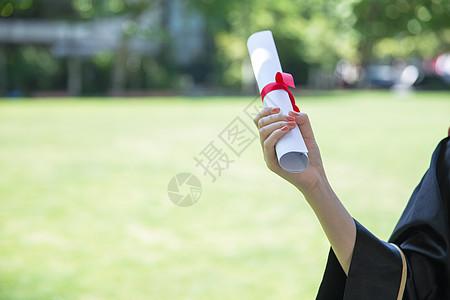 草地上手拿毕业证的毕业生图片