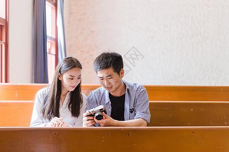 男女大学生在教室看相机照片图片