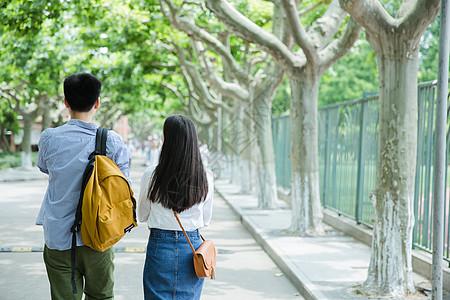 青春男女学生走在校园路上背影图片