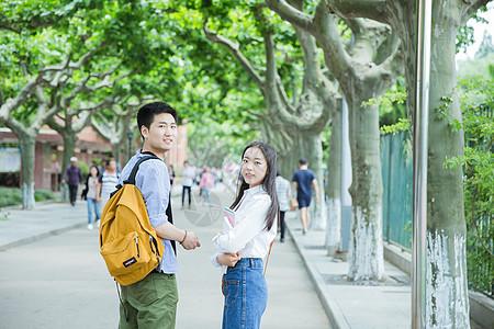 青春男女学生走在校园路上回头图片