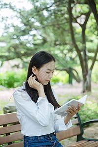 清新女大学生坐在椅子上看书图片